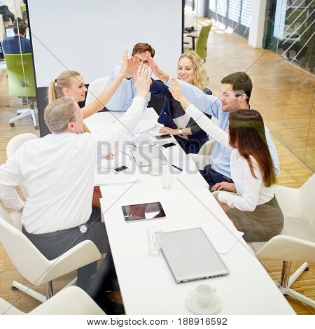 Business team with high five in a conference as a success concept