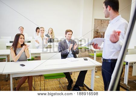 Audience applauding in a business seminar after a presentation