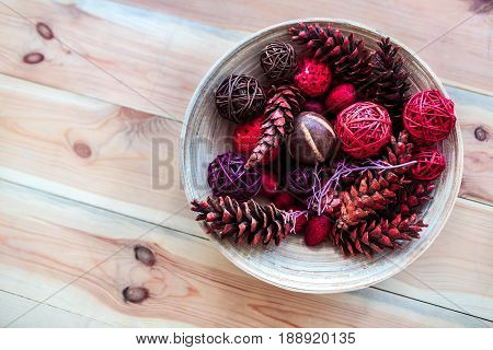 Wooden decoration plate with rattan balls and pine cones. Top view