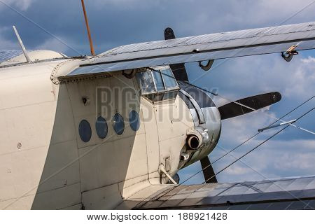 Old propeller biplane against cloudy sky closeup