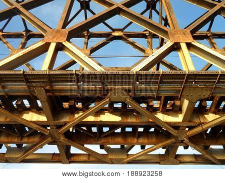 metal construction of old railway bridge, details in golden colour, can be used as a background