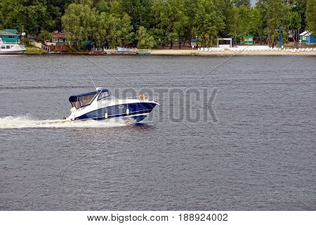 An excursion yacht swims to down the river along with the coast