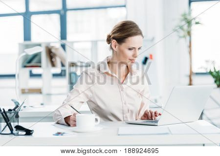 Young Caucasian Businesswoman In Formalwear Working On Laptop At Office