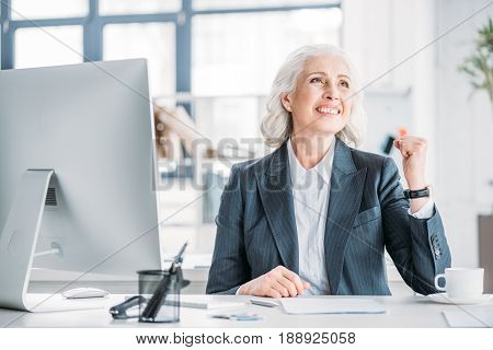 Cheerful Senior Businesswoman In Formal Wear Sitting At Workplace And Triumphing