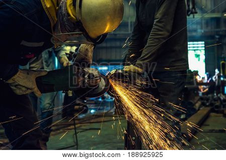 Worker using electric wheel grinding on steel structure in factory.