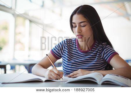 Attentive schoolgirl doing homework in classroom at school