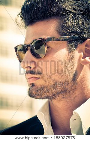 Handsome and attractive young man outdoor. Charming style, with sunglasses and shirt. Short beard, warm colors. Masculine beauty.