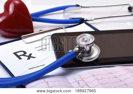 Closeup of stethoscope on a rx prescription, red heart and phone isolated on white background