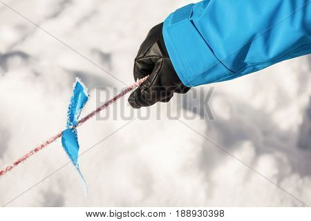 Skier holding pole in the snow on a bright sunny day