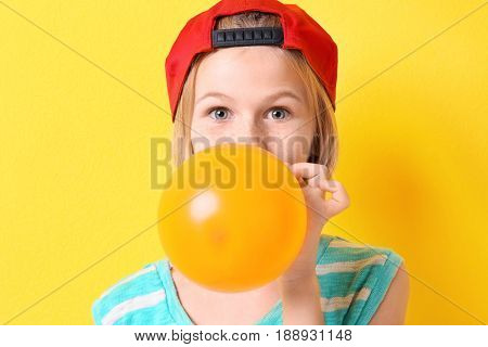 Funny teenager girl in red hat inflating balloon on yellow background