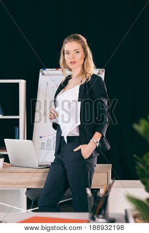 Confident Young Businesswoman With Hand In Pocket Holding Papers And Looking At Camera