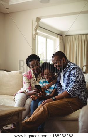 Family using mobile phone in living room at home
