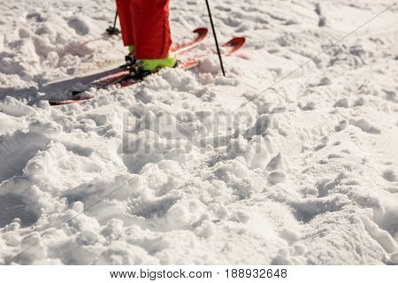 Low section of skier standing on snowy mountains