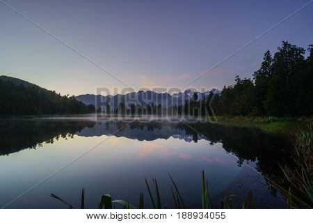 Beautiful reflection of Lake Matheson in twilight at sunrise with mist and Mount Cook /Aoraki and Mount Tasman South Island of New Zealand