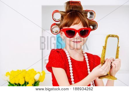 Portrait of a funny little girl with curlers in her hair and modern red dress. Kid's fashion. Family at home.