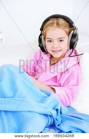 Cute girl listens to music in headphones at home. Leisure. Family at home.