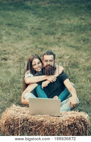 Couple in love Smiling adorable girl or cute woman and bearded man hipster with beard with long hair using laptop on hay bale on grass on summer day on natural background. Technology nature