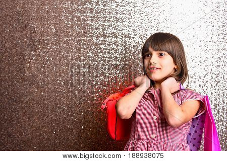 small pretty girl or cute fashionable child with long brunette hair and adorable smiling happy face in checkered dress with red leather bag and shopping package on metallic background copy space