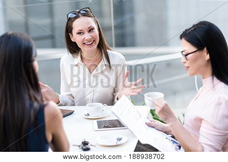 Cheerful businesswoman flourishing arms while making conversation with colleagues in cafe