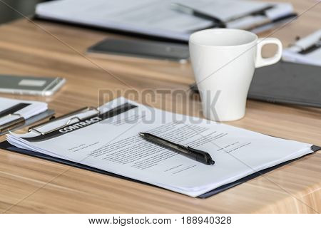Smartphones With Contract And Notebooks With Stapler On Table At Modern Office
