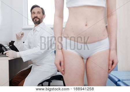 Improving figure. Handsome enthusiastic qualified doctor consulting young lady about the plastic surgery she wanting doing for changing her figure