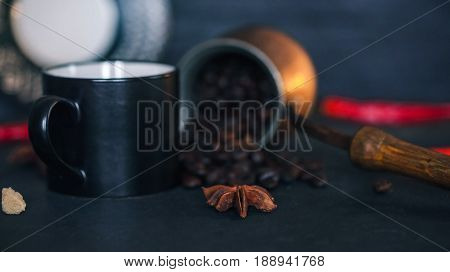 Coffee beans scattering off copper coffee pot. Black coffee cup and red hot chili peppers on black slate surface
