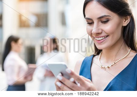 Female demonstrating cheerfulness while writing message by phone on street