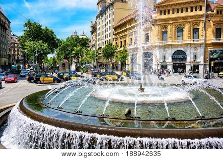 Barcelona Spain - June 6 2016: Fountain in the center of a roundabout in the city busy with pedestrians and traffic.