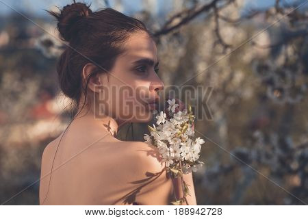 girl or sexy woman with hair bun and naked shoulders posing with blossoming white flowers in garden on sunny spring day on blurred natural environment. Springtime youth and loneliness