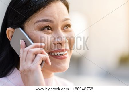 Close up portrait face of female demonstrating happiness while speaking by phone