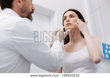 I want look younger. Concerned beautiful charismatic lady seeking experts advice while trying explaining him the things about her look which concerning her the most