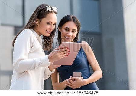 Happy lady with beaming associate looking at screen of electronic tablet outdoor