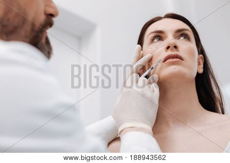 Perfect skin again. Smart charismatic motivate lady trusting her face to specialist who performing a cosmetic surgery while injecting her skin with botox