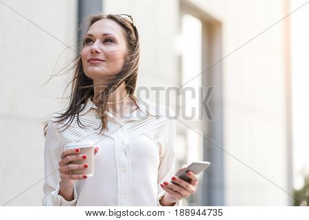 Woman demonstrating wistfulness while writing message by mobile. She tasting mug of beverage