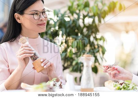 Portrait of happy asian lady holding caster in arms while making conversation with colleague in cafeteria