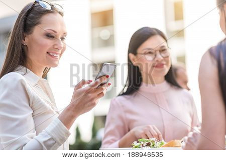 Low angle businesswoman demonstrating cheerfulness while looking at mobile in restaurant