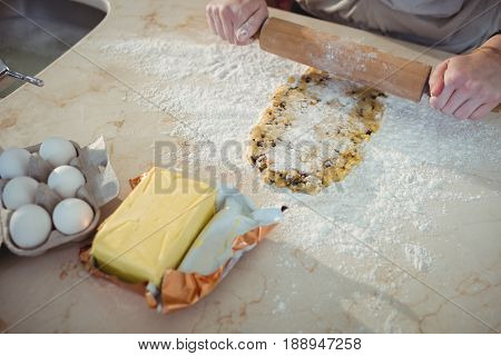Hands sheeting the dough with rolling pin in kitchen at home