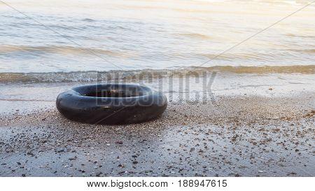 Clouse up black swim ring / swim tube / inner tube on sandy beach with sunlight
