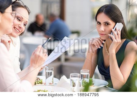 Female expressing seriousness while telling by mobile. She sitting at table in cafe