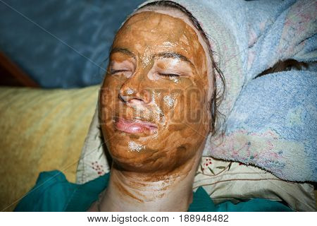 Spa At Home. Young Girl Of 20 Years Old Lies With Natural Facing Mask On Her Face And Towel On Her H