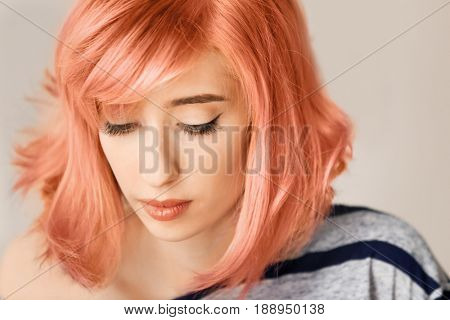 Trendy hairstyle ideas. Young woman with dyed apricot hair on color background