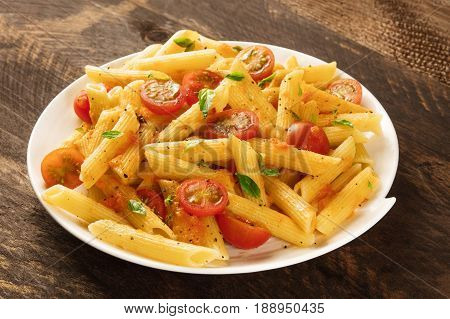 A photo of a plate of pasta with tomato sauce. Penne rigate with cherry tomatoes and fresh basil leaves, on a dark rustic texture