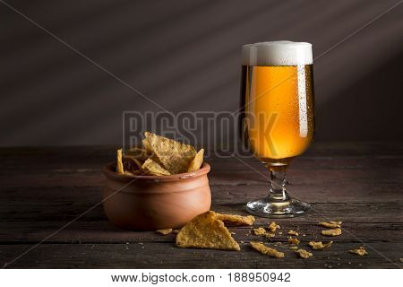 Glass of cold pale beer with a bowl of crisps on a rustic wooden table