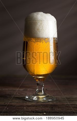 Glass of cold pale beer with a bowl of peanuts on a rustic wooden table