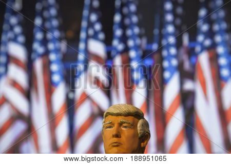 Caricature of United States President Donald Trump  - Head above water concept - using a toy action figure with US Flag backdrop - filtered image