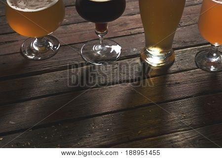 Detail of pale dark unfiltered pale and red fruit beer in four different beer glasses on a rustic wooden table.