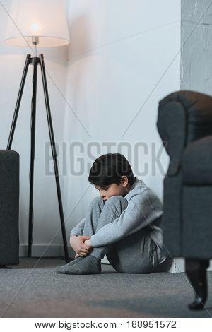 Upset Little Kid Boy Sitting At Corner At Home