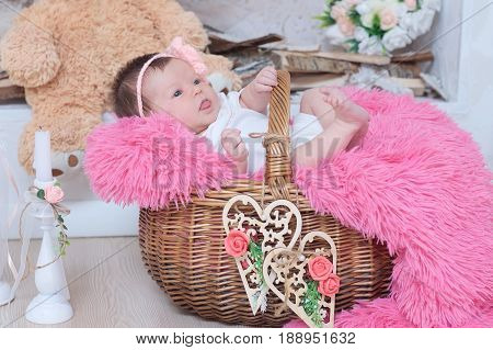 newborn baby girl in basket cute decoration with pink blanket candles toy bear and hearts. New child announcement