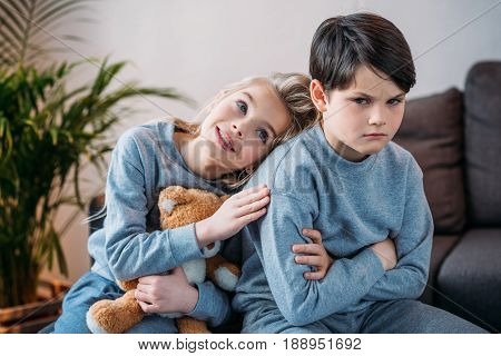Adorable Girl Embracing Offended Boy Sitting On Sofa At Home