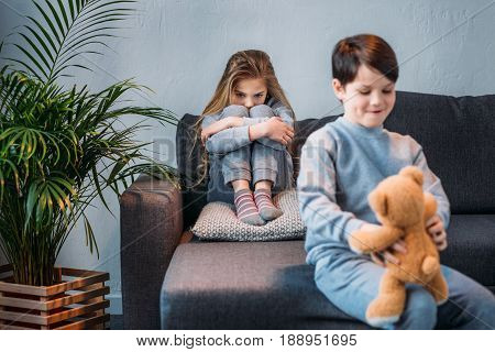 Sly Boy Holding Teddy Bear While Offended Girl Sitting On Sofa Behind